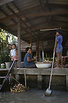 A family draws water from a klong to prepare supper. People live on the klongs, boulevards of water that flow through the city like open veins, and spend their lifetimes living in houseboats or  canal front houses in Bangkok, Thailand. (Jim Bryant Photo)...