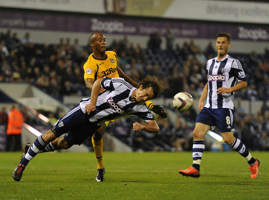 West Bromwich Albion's Diego Lugano heads the ball away from the foot of Newport County's Chris Zebroski<br /> <br /> Photo by Ashley Crowden/CameraSport<br /> <br /> Football - Capital One Cup Second Round - West Bromwich Albion v Newport County - Tuesday 27th August 2013 - The Hawthorns - West Bromwich<br />  <br /> &copy; CameraSport - 43 Linden Ave. Countesthorpe. Leicester. England. LE8 5PG - Tel: +44 (0) 116 277 4147 - admin@camerasport.com - www.camerasport.com