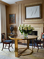 In the dining room, which is panelled in oak, a 1970s dining table by Maison Jansen sits atop a vintage rug, the painting above the fireplace is by Lucio Fontana, and the 18th-century painting is by Giambattista Pittoni.
