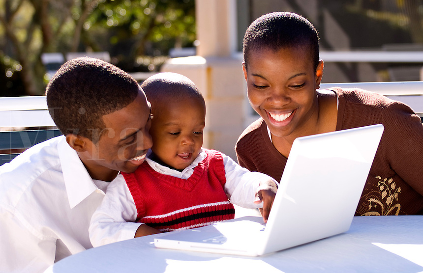 Attractive black African American family with young boy playing with computer at home in sunshine outdoors smiling and happy