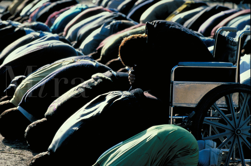 TITLE;DISTANT RELATIONS, PALESTINIANS PRAYING, MAN IN WHEELCHAIR BOWS TO MECCA, MOSLEM, PRAYER,.