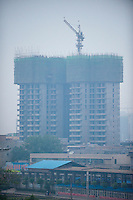 Daytime vertical view from the Xī'ān chéngqiáng of a commercial building under construction in the Xī'ān Shì Weiyang District in Shaanxi Province.  © LAN