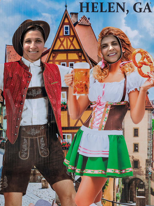 Tourists pose in German Octoberfest motif cut-out, Helen, Georgia, USA.