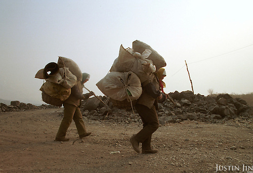 Workers carry goods from the garbage dump  home at the end of the day...Between 50-100 Chinese from a small village in southwestern China's Sichuan province live and work here, one thousand miles away from home. They are part of a cooperative selling scraps and wastes to local farmers and factories...They look for bits of wire, bottles and plastics that they can re-sell. They earn about 300 yuan (US$36) a month per person, which is low by urban standards but is about 10 times as much as wages at home in Sichuan....Picture taken March 1999.Copyright Justin Jin