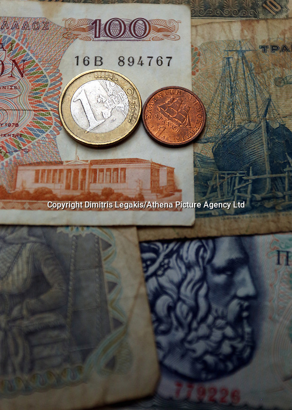 An o ld drachma coin and a one euro coin on old drachma paper notes