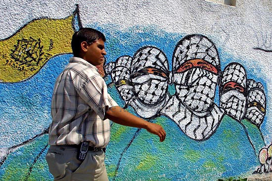A Palestinian man passes by graffiti of militants of the Fattah faction, The Martyrs of Al Aqsa brigades, outside the Al Quds University in Gaza City. Photo by Quique Kierszenbaum