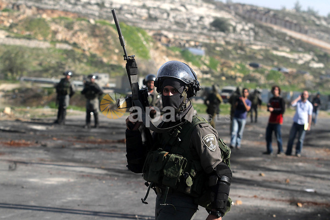 A masked Israeli soldier carries his M16 during clashes next to the Israeli military prison Ofer, south of the West bank city of Ramallah, 21 February 2013. Reports state that the protest is in support of Palestinian prisoners on hunger strike held in Israeli prisons. Photo by Issam Rimawi