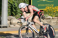 A man triathlete finishing her bike session at the ChelanMan Multi-Sport Weekend in Chelan