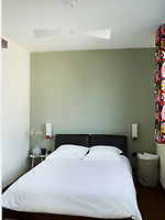 In the bedroom, one wall is painted in a pale green. The double bed has an upholstered leather headboard and the windows are dressed in patterned print fabric curtains. A retro style ceiling pendant hangs above the bed.