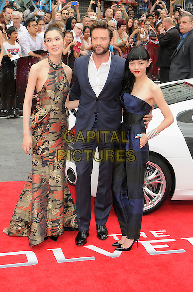 Tao Okamoto, Hugh Jackman and Rila Fukushima<br /> &quot;The Wolverine&quot; UK Premiere, Empire Leicester Square, London, England.<br /> 16th July 2013<br /> full length white shirt beard facial hair suit blue brown red sleeveless pattern dress strapless jumpsuit black hand on hip green in pocket <br /> CAP/PP /BK<br /> &copy;Bob Kent/PP/Capital Pictures