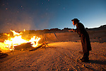 A man prays next to a fire in a construction site, which was set by ultra-Orthodox Jewish men protesting against the construction of a new neighborhood, in the town of Ramat Beit Shemesh. They claim the designated construction area is full of ancient burial caves.