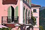 A pink building/hotel with green shudders in Morcote, a town on Lake Lugano, Switzerland
