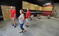 NWA Democrat-Gazette/MICHAEL WOODS • @NWAMICHAELW<br /> Arkansas Music Works owners Tony Baker (from left) Christina Baker and Gregg Price walk through the main room of their new store September 23, 2015 as workers prepare it for the grand opening in early October.  The new location will include more warehouse space for their online sales services as well more classroom space for music lessons.  The new location is expected to open for business October 7th.