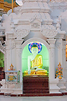Myanmar, Burma.  Shwedagon Pagoda, Yangon, Rangoon.  Small Buddha Shrine with the Buddha demonstrating the mudras (hand gestures) of earth-touching (bhumisparsha) and wisdom (dhyana).