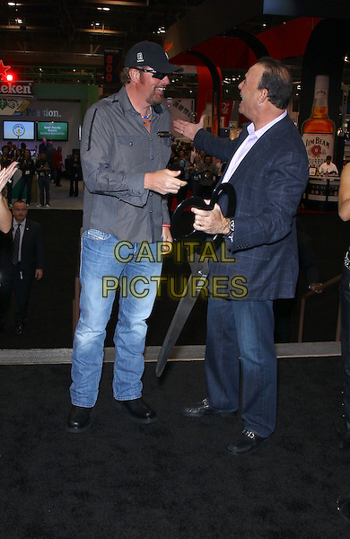 Toby Keith, Jon Taffer.Superstar Toby Keith and Jon Taffer conduct the ribbon cutting ceremony for the 27th Annual Nightclub & Bar Convention and Trade Show at the Las Vegas Convention Center, Las Vegas, Nevada, USA..March 13th, 2012.full length grey gray shirt sunglasses shades black baseball cap hat jeans denim  ribbon giant oversized scissors side profile  .CAP/ADM/MJT.© MJT/AdMedia/Capital Pictures.