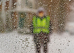 Merrick, New York, U.S. January 21, 2014. A School Crossing Guard wearing a neon green safety vest is seen through a car window coated with snow, when schools close early. Governor Cuomo declared a state of emergency due to the snow storm, with up to 10 inches of snow expected.