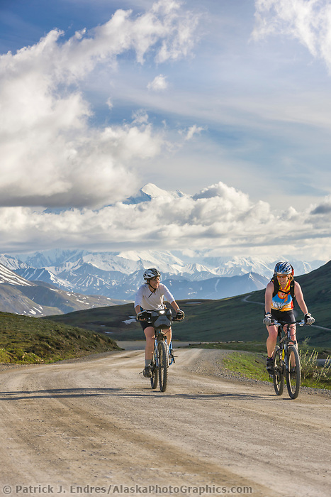 Women biking along the Denali Park Highway, Mount McKinley visible in the distance.