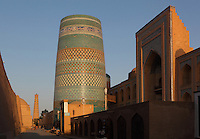 General view of Matniyaz Divan-begi madrasah (right) 1871, Kalta Minor (centre) 1855, and Juma minaret, 10th-13th centuries, Khiva, Uzbekistan, pictured on July 7, 2010, at sunset. The Kalta Minor or Short Minaret was commissioned by Mohammed Amin Khan in 1852 to stand 70 m. high, but was abandoned when he died in 1855, and remains only 26 m. high. Commissioned by Muhammad Niyaz, the rectangular Matniyaz Divan-begi madrasah has a traditional main facade, its high portal, decorated with majolica, having a central pentahedral niche and corner guldastas which are geometrically patterned in blue, white and green, with green brick domes. The Juma minaret, oldest in Khiva, has a tapering brick trunk decorated with seven narrow belts of small turquoise bricks. Khiva, ancient and remote, is the most intact Silk Road city. Ichan Kala, its old town, was the first site in Uzbekistan to become a World Heritage Site(1991). Picture by Manuel Cohen.