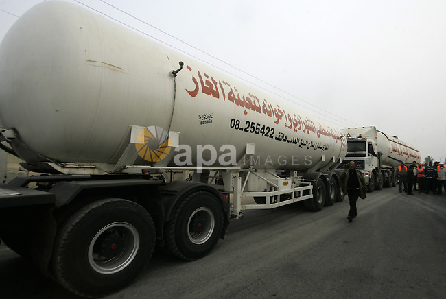 A Palestinian worker walks past an oil trucks in the Palestinian Rafah border crossing while the oil trucks are preparing to go to bring fuel from crossing Karem Salem Israeli , in the southern Gaza Strip on November 29, 2010. Photo by Abed Rahim Khatib