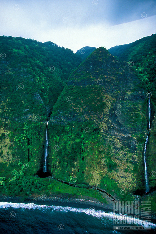 Two cascading waterfalls cut through the lush green mountains on the North Kohala coast of the Big Island of Hawaii.