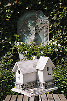 A white-painted Dutch bird house is supported by the garden table on the patio