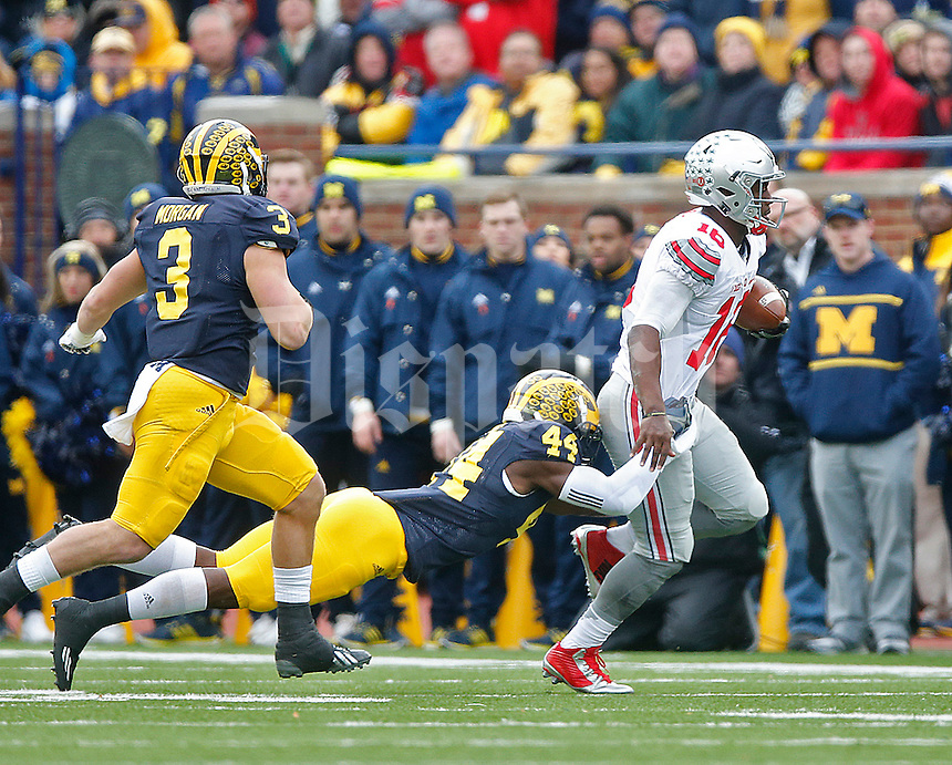Ohio State Buckeyes quarterback J.T. Barrett (16) drags Michigan Wolverines safety Delano Hill (44) for a ride at Michigan Stadium on November 28, 2015. (Chris Russell/Dispatch Photo)