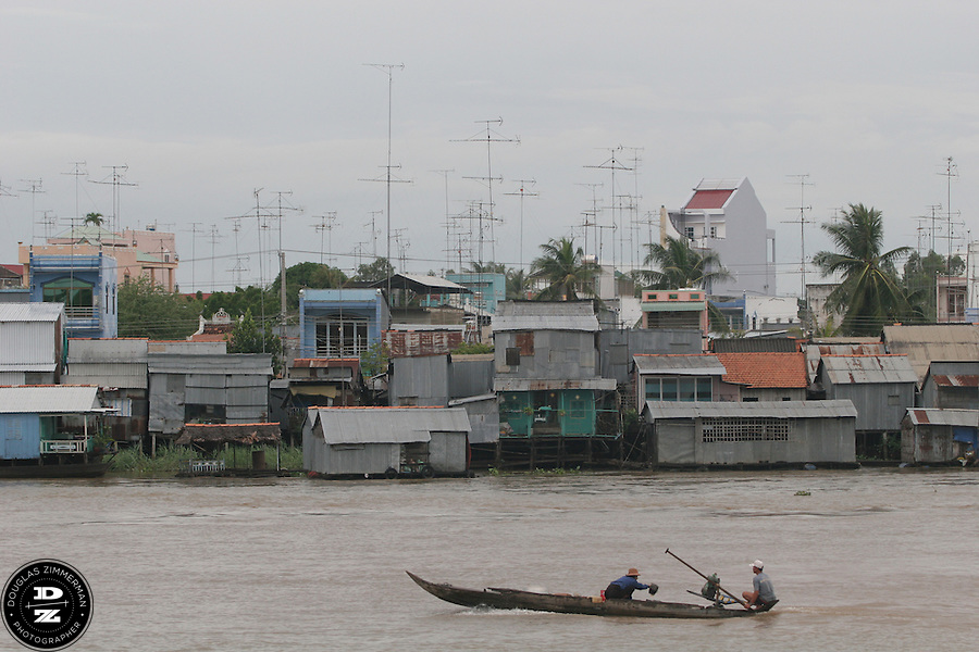 Houses line the shores of Chau Doc, Vietnam  along the Bassac River in the Mekong Delta.  The Mekong Delta has long been the watery  thoroughfare for the many villages that dot the riversides of the delta.  Many of the villages have floating markets where people can buy produce and other items from wholesalers.  Photograph by Douglas ZImmerman