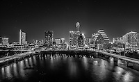 The city of Austin skyline after dark from across ladybird lake between congress and south first with iconic buildings like the Frost, 360 Condos, and Austonion all showing in the view in this black and white image of the city.