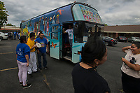 NWA Democrat-Gazette/J.T. WAMPLER People tour a decorated bus Monday Sept. 10, 2018 during a press conference at the Northwest Arkansas Workers Justice Center in Springdale. The National TPS Alliance is taking a bus across the country to raise awareness for the 450,000 people in the U.S. protected by Temporary Protected Satus.