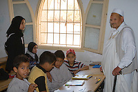 "Surman, Libya.  Boys and Girls Memorizing the Koran in the Madrasa of Sidi Rashid al-Galili.  They study under the supervision of Bashir, a ""muqri"".  He wears the traditional ""holi"" or ""jard"", a white cloak.  Young girls wear the traditional Libyan head scarf.  Boys may wear traditional garments, but western or European sport shirts or T-shirts are more popular."