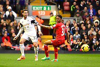 Sunday, 23 February 2014<br /> Pictured: Swansea City's Angel Rangel and Liverpool's Raheem Sterling compete for the ball<br /> Re: Barclay's Premier League, Liverpool FC v Swansea City FC v at Anfield Stadium, Liverpool Merseyside, UK.