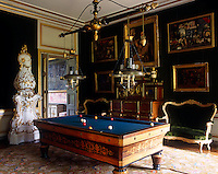 The billiard room is furnished with an antique biliard table with impressive pendant lights