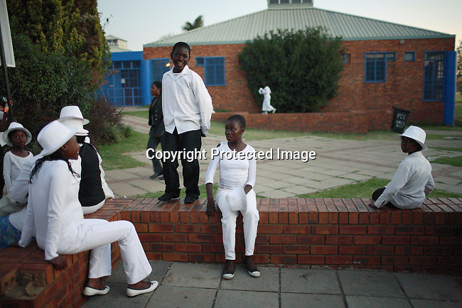 Members of a church choir wait for their transport after performing at a church function.