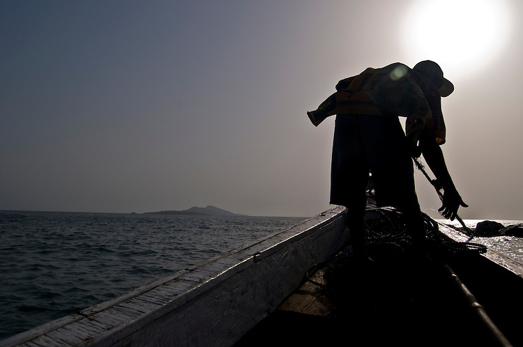 Man pulling in the anchor on a boat, with the Banana Islands in the background. Sierra Leone. Photo taken February 22, 2010.