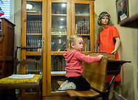 STAFF PHOTO JASON IVESTER --12/12/2014--<br /> Hope Kebert (cq), 2, of Lowell sits in a school desk on Friday, Dec. 12, 2014, inside the Lowell Historical Museum. The museum hosted a Christmas open house to visitors.