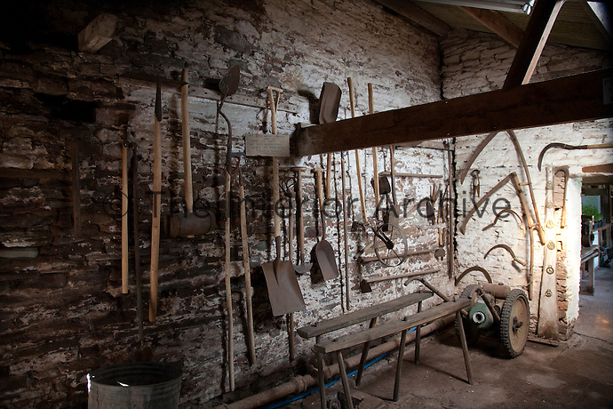 Gardening tools hung up in an ancient outbuilding
