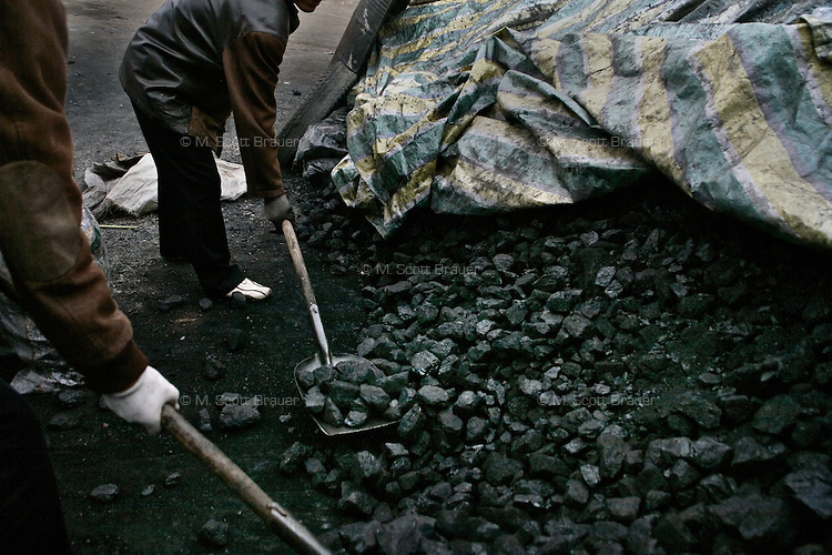 Workers shovel coal in a small market in Xiahe, Gansu, China.  Xiahe, home of the Labrang Monastery, is an important site for Tibetan Buddhists.  The population of the town is divided between ethnic Tibetans, Muslims, and Han Chinese.