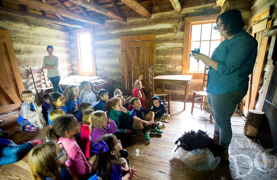 NWA Democrat-Gazette/JASON IVESTER<br /> Carly Squyres (cq), education assistant, talks to Elm Tree Elementary first-graders on Thursday, May 19, 2016, inside the cabin at the Shiloh Museum of Ozark History in Springdale. The five first-grade classes from the Bentonville school visited the museum as they begin their studies on Arkansas history.