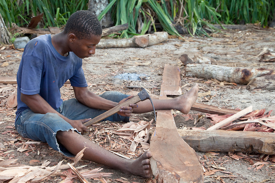 Nungwi, Zanzibar, Tanzania.  Dhow Construction, Boat Building.  Carpenter working with an Adze.  The small blue line remaining near the tip of the blade of the adze indicates the line he is following in shaping the plank.