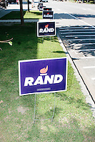 Political signs for Kentucky senator and Republican presidential candidate Rand Paul  stand in the grass outside Kilton Library for a town hall campaign event in West Lebanon, New Hampshire.