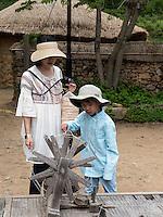 Touristen am Spinnrad im Folk-village Naganneupsong-ehemalige Festung, Provinz Jeollanam-do, Südkorea, Asien<br /> tourists with spinning wheel  in Folk-village Naganneupsong- a former fortress, province Jeollanam-do, South Korea, Asia