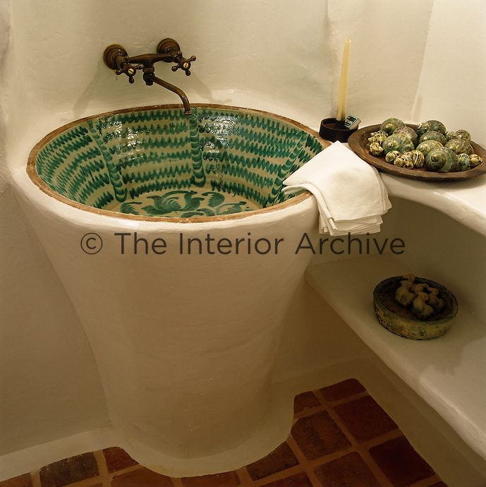 A local hand-painted ceramic bowl has been made into a wash basin in the corner of this bathroom