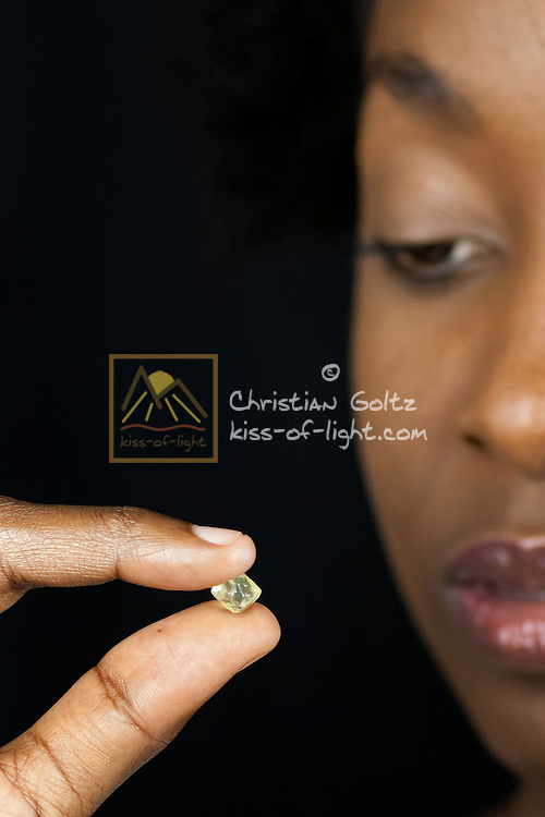A black Namibian model inspects a diamond from the Sperrgebiet (Diamond Area 1)