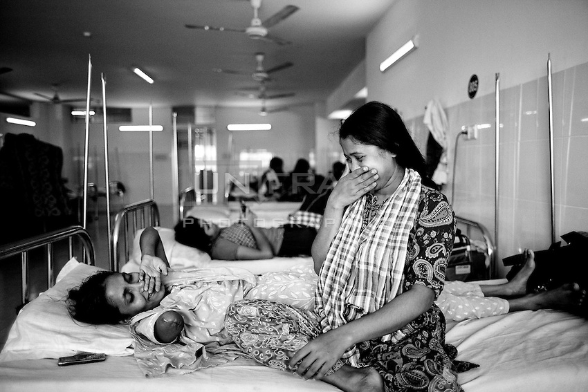 Bangladeshi garment worker Mariyam, 30, who worked on the 6th floor of Rana Plaza,with her syster at Enam Medical College, in Savar, near Dhaka, Bangladesh. Mariyam had her right arm amputated to free her from the rubble when she was rescued nearly 72 hours after the building collapsed.