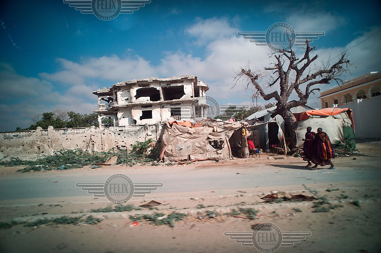 A view of a temporary residence in front of a destroyed building, a result of 21 years of civil war, in Mogadishu.