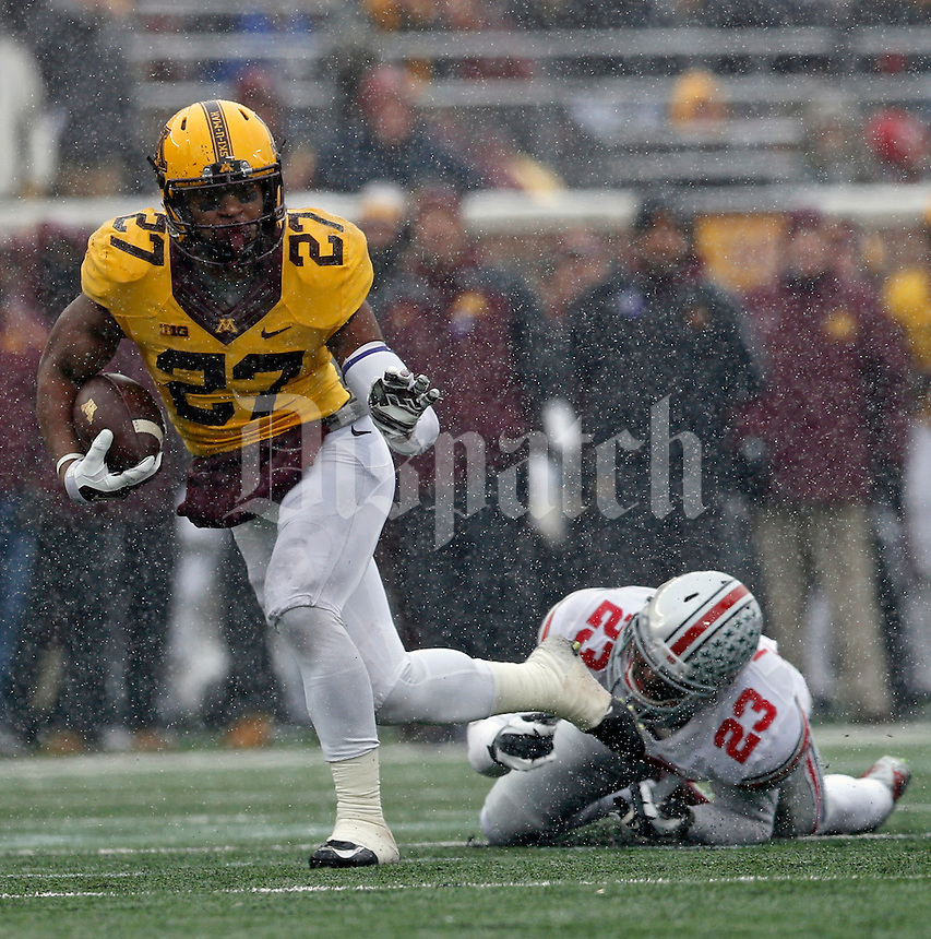 Minnesota Golden Gophers running back David Cobb (27) shakes off Ohio State Buckeyes safety Tyvis Powell (23) for a touchdown run during the 2nd quarter at TCF Bank Stadium in Minneapolis, Minn. on November 15, 2014.  (Dispatch photo by Kyle Robertson)