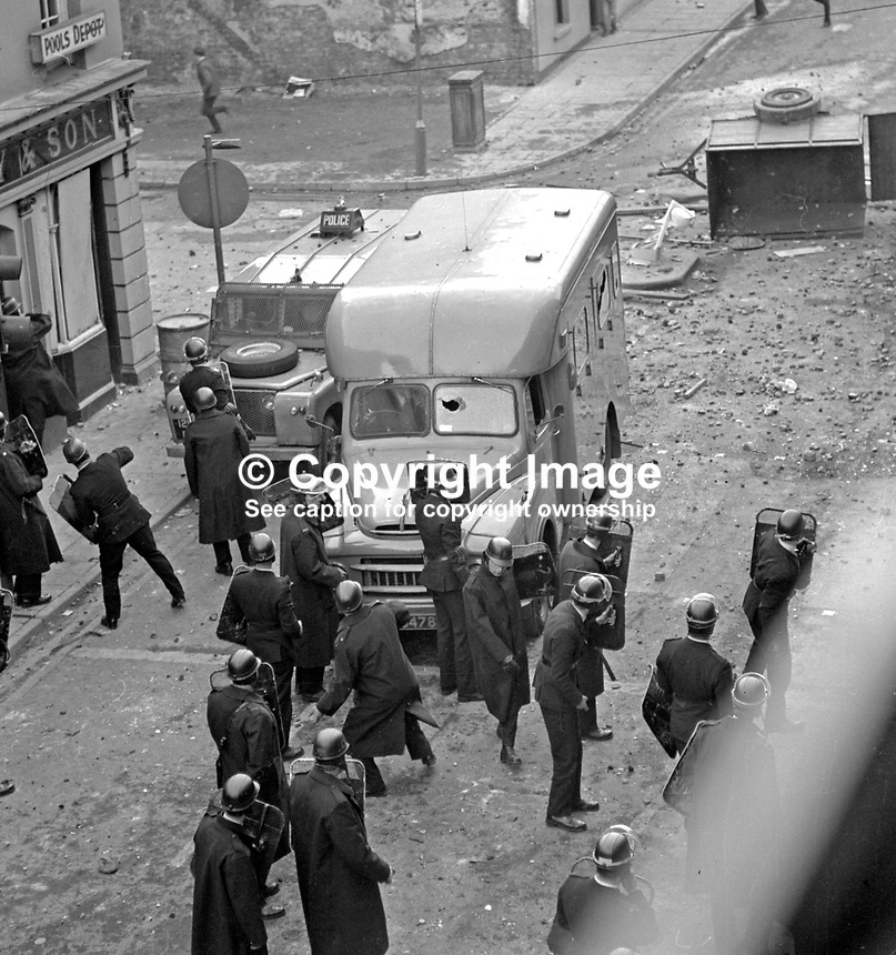 RUC riot police shelter from missiles behind police vehicles in William Street during the Battle of the Bogside, Londonderry, N Ireland, UK.  196908140010<br /> <br /> Copyright Image from Victor Patterson, 54 Dorchester Park, Belfast, UK, BT9 6RJ<br /> <br /> t1: +44 28 9066 1296 (from Rep of Ireland 048 9066 1296)<br /> t2: +44 28 9002 2446 (from Rep of Ireland 048 9002 2446)<br /> m: +44 7802 353836<br /> <br /> e1: victorpatterson@me.com<br /> e2: victorpatterson@gmail.com<br /> <br /> The use of my copyright images is subject to my Terms &amp; Conditions.<br /> <br /> It is IMPORTANT that you familiarise yourself with them. They are available on my website at www.victorpatterson.com.<br /> <br /> None of my copyright images may be used on a website unless they are visibly watermarked, i.e. &copy; Victor Patterson within the body of the visible image. Metadata denoting my copyright must NOT be deleted. <br /> <br /> Web use is extra at currently recommended NUJ rates.