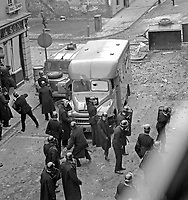 RUC riot police shelter from missiles behind police vehicles in William Street during the Battle of the Bogside, Londonderry, N Ireland, UK.  196908140010<br />