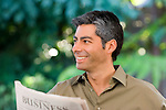 Hispanic man reading newspaper, smiling