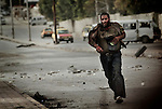 As he approached the other side of the street, he was shot a second time, falling to the ground. Free Syria Army soldiers crawled through the ground to reach him and pulled them towards a vehicle that rushed him to the hospital. It is not known if he survived. Three civilians were shot on this main road in the space of three hours by the same sniper. ..© Javier Manzano.....